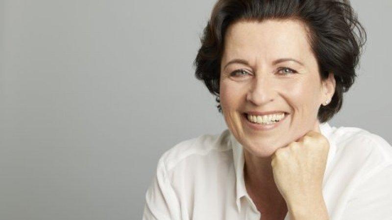 Eva-Maria Zurhorst hat das Kinn in die Hand gestützt und lacht in die Kamera