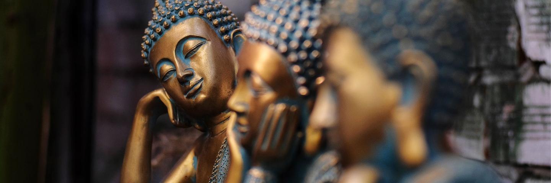 Drei goldene Buddha-Statuen in jeweils unterschiedlicher Haltung. Die vordere ist nur unscharf zu erkennen, die zweite hat den Kopf in die Hände gestützt, die dritte neigt den Kopf zur Seite.