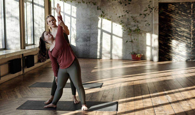 Eine Yogalehrerin hilft ihrer Schülerin, die Haltung einer Yoga-Pose zu verbessern