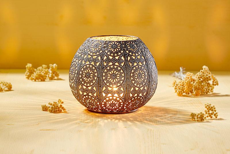 Ein Windlicht mit orientalischem Lochmuster steht auf einem Tisch vor einem gelbem Hintergrund. Im Inneren brennt eine Kerze.