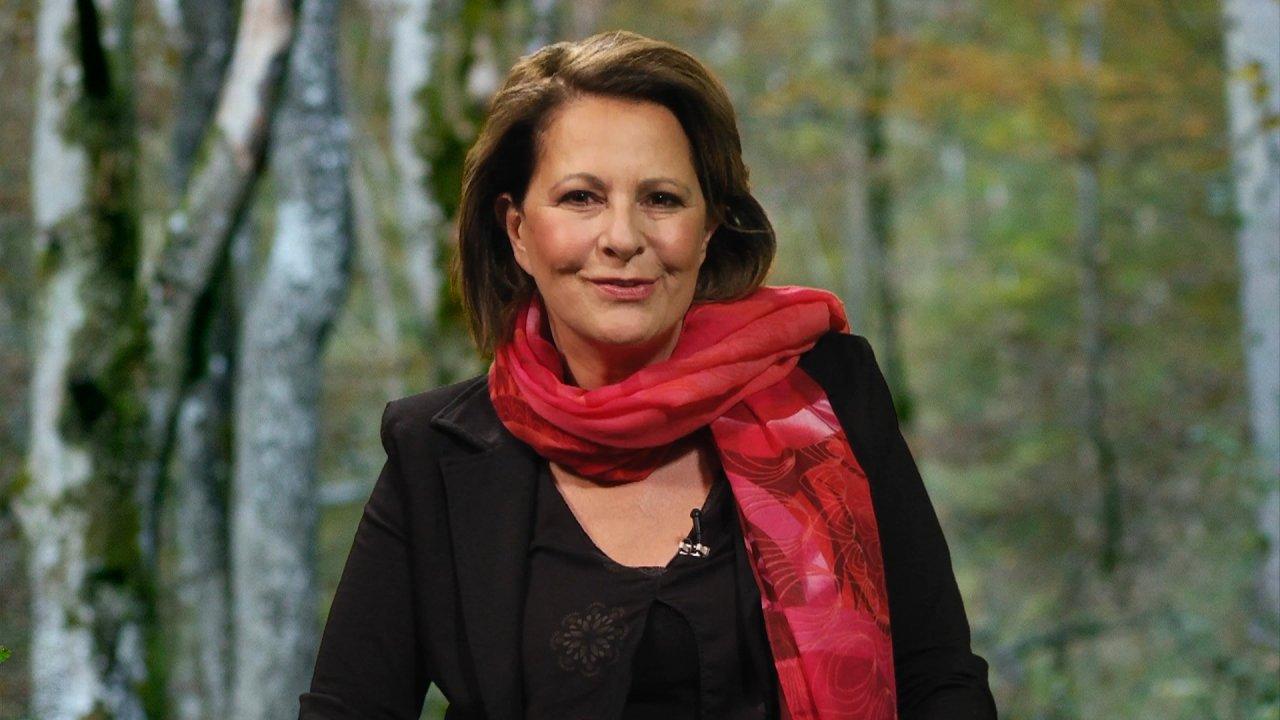 Stefanie Stahl trägt ein schwarzes Kleid und einen roten Schal und schaut lächelnd in die Kamera