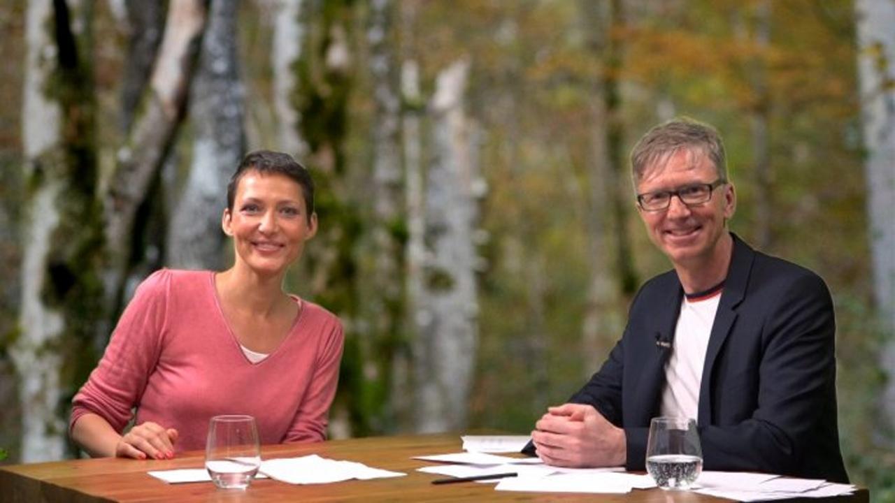 Ina Rudolph und der Moderator des Webinars sitzen an einem Tisch und lächeln in die Kamera