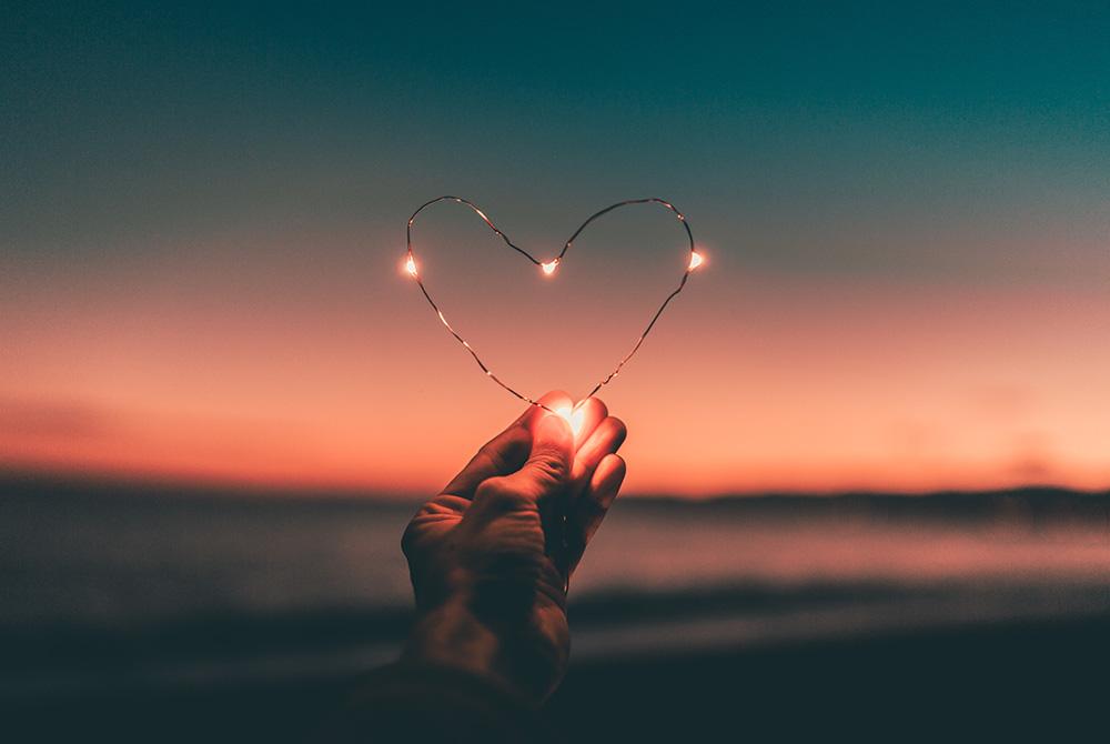 Vor einem Sonnenuntergang hält eine Hand ein Herz aus Draht in die Kamera. Das Herz leuchtet an mehreren Stellen.