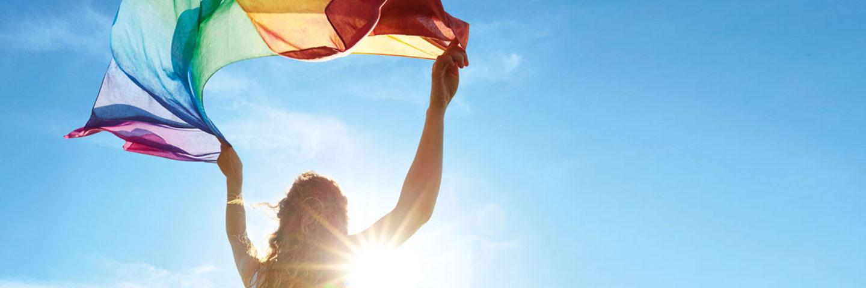 Frau schwingt einen Schal in Regenbogenfarben vor blauem Himmel. Die Sonne blitzt hinter ihr hervor.