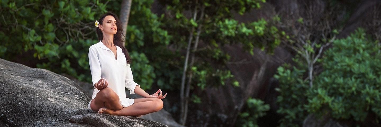 Weiß gekleidete Frau mit Blüte im Haar meditiert auf einem Fels, im Hintergrund Bäume