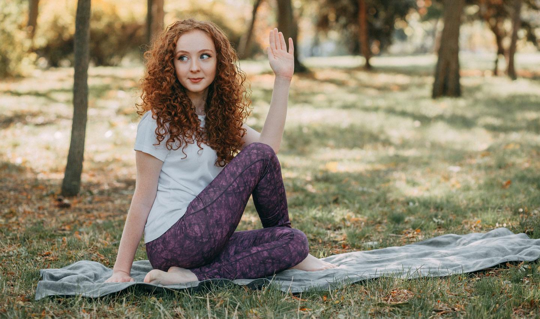 """Junge Frau übt die Yoga-Pose """"Drehsitz"""" in einem Park"""