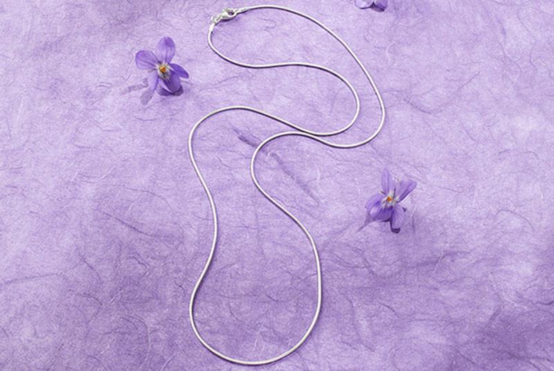 Eine schlichte Silberkette liegt auf einem violetten Untergrund, daneben violette Veilchenblüten.