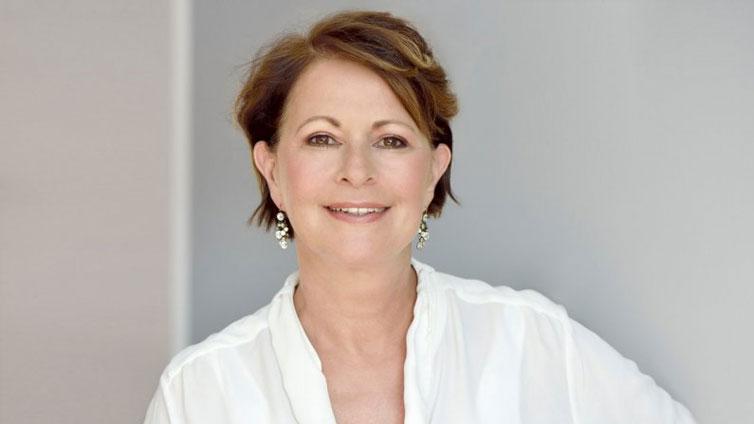 Porträt von Stefanie Stahl. Sie trägt eine weiße Bluse und passende Ohrringe und lächelt in die Kamera