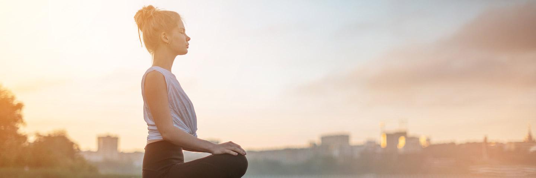 Eine junge Frau sitzt im Schneidersitz und hat die Hände auf den Knien abgelegt. Sie meditiert, während im Hintergrund die Sonne aufgeht.