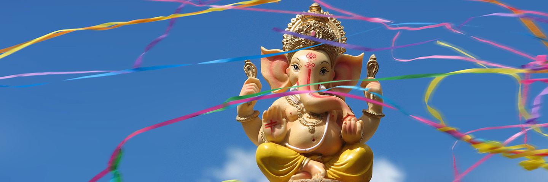 Ganesha-Statue vor blauem Himmel, umgeben von bunten Luftschlangen