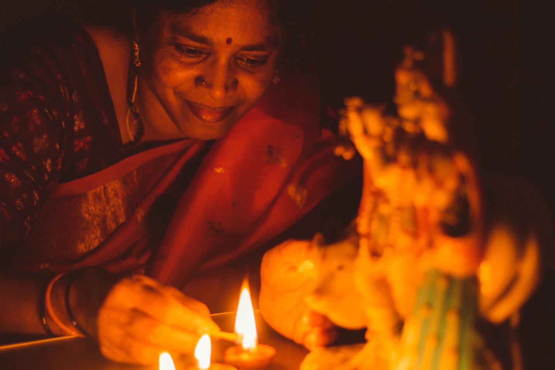 Eine indische Frau zündet vor dem Bildnis einer Gottheit lächelnd eine Kerze an