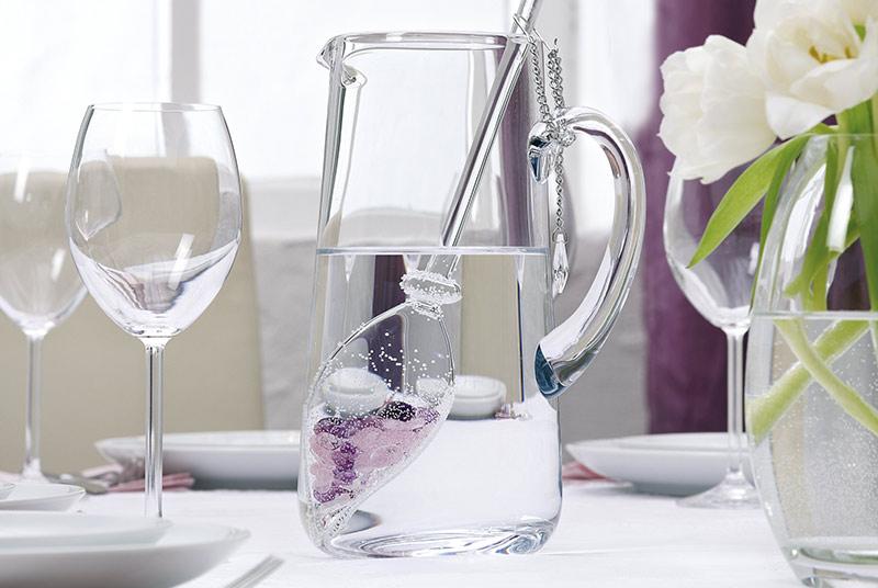 Auf einem gedeckten Tisch steht eine Glaskaraffe, darin ein Vita-Juwel-Stab mit Edelsteinen. Rechts daneben steht eine Vase mit weißen Tulpen.