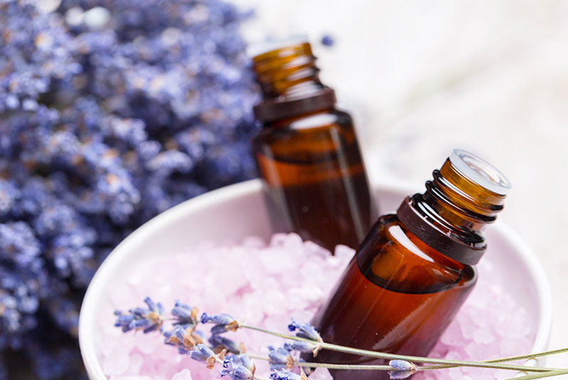 Zwei kleine braune Fläschchen ohne Deckel stehen in einer kleinen weißen Schale, die mit Badesalz gefüllt ist. Im Vordergrund und Hintergrund liegt getrockneter Lavendel.