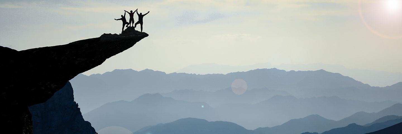 Silhouette eines Teams aus drei Menschen auf einem Felsvorsprung