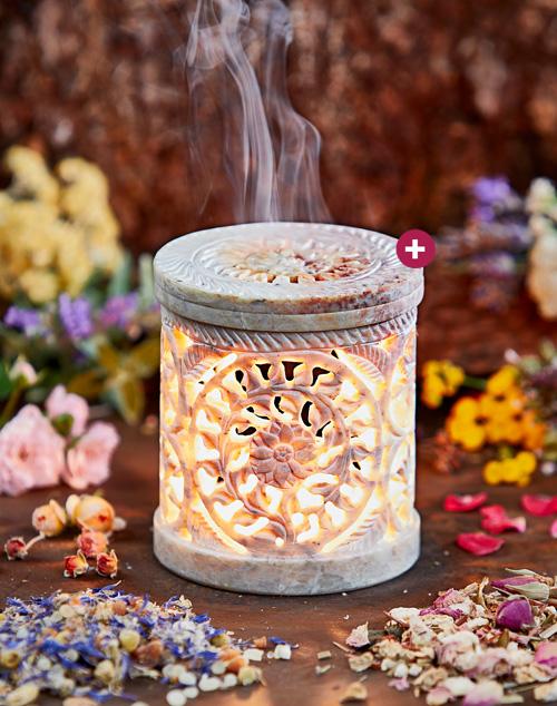 Produkt: Helles, erleuchtetes Räucherstövchen mit Deckel, aus dem Rauch austritt. Im Hintergrund bunte Blüten.