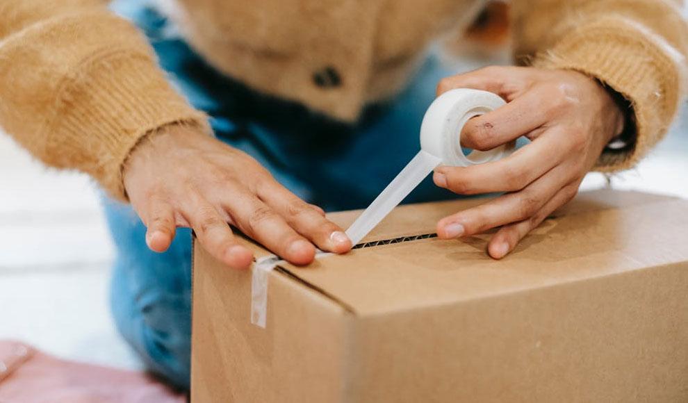 Eine Person kniet hinter einem Paket und verschließt es mit Klebeband.