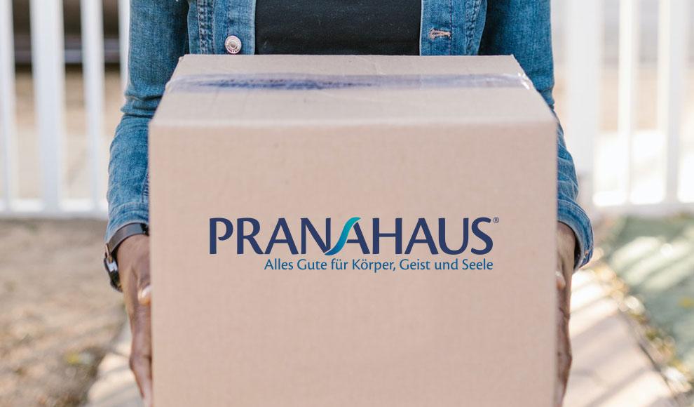 Eine Person hält ein Paket mit dem PranaHaus-Logo in Richtung der Kamera.