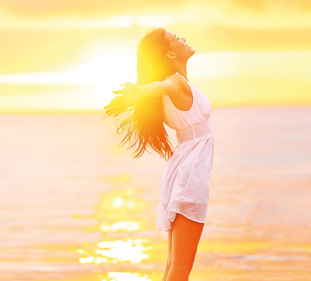 Eine Frau steht mit ausgebreiteten Armen während dem Sonnenuntergang am Meer