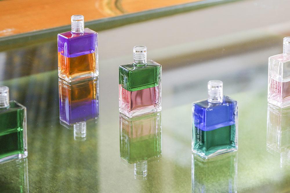 Mehrere Aura Soma-Equilibrium-Flaschen auf einem Glastisch