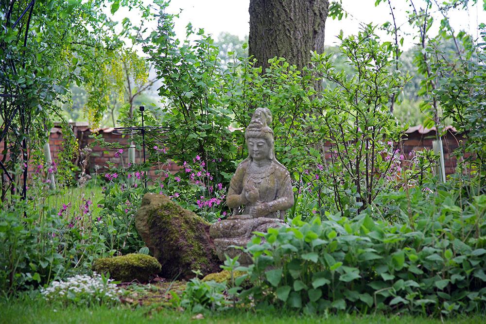Üppiger Garten mit Grünpflanzen, in dessen Mitte eine steinerne Buddha-Statue sitzt.