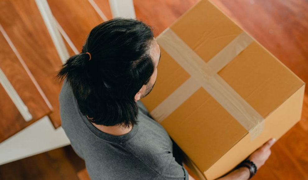 Eine Person trägt ein großes Paket