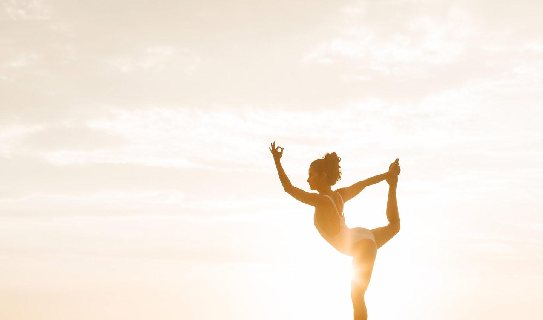 """Eine Frau übt die Yoga-Pose """"Der Tänzer"""" unter freiem Himmel"""
