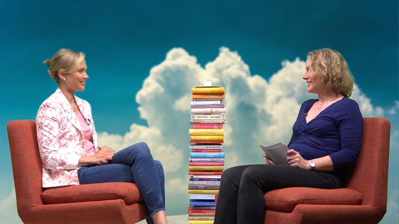 Jana Haas und die Moderatorin sitzen in Sesseln, zwischen ihnen ein hoher Stapel mit Büchern. Sie sind einander zugewandt.