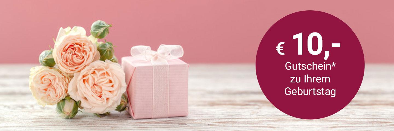 """3 hellrosa Rosen liegen auf einem weißen Holztisch, daneben ein kleines, in rosa Papier eingepacktes Geschenk mit weißer Schleife. Rechts im Bild ein dunkelroter Kreis mit weißem Text: """"10€ Gutschein zu Ihrem Geburtstag"""""""