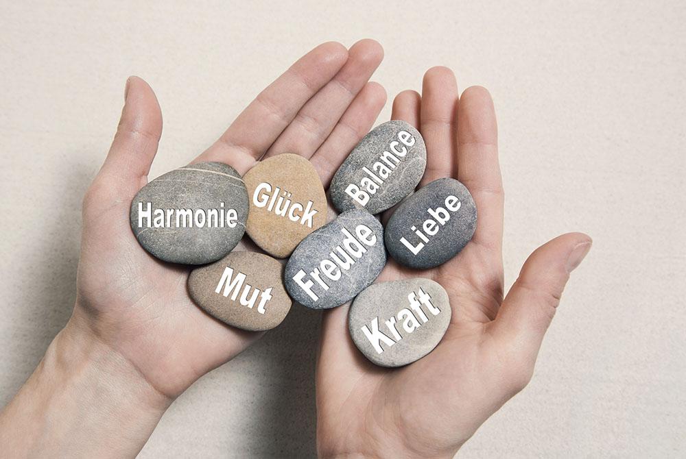 Zwei Hände halten mehrere große Kiesel, auf denen die Worte Harmonie, Glück, Mut, Freude, Balance, Kraft und Liebe zu lesen sind