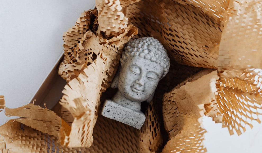 Eine kleine steinerne Budda-Statue liegt in einem geöffneten Päckchen.