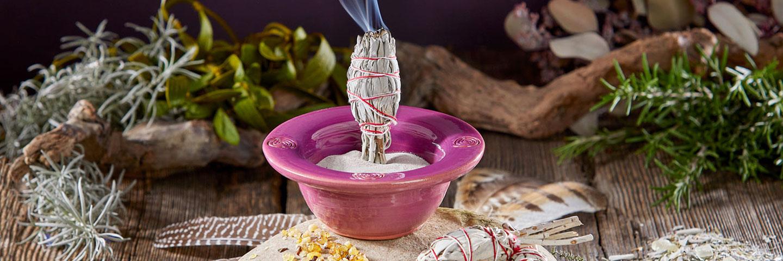 Eine violette Räucherschale steht in einem Arrangement aus verschiedenem Räucherwerk