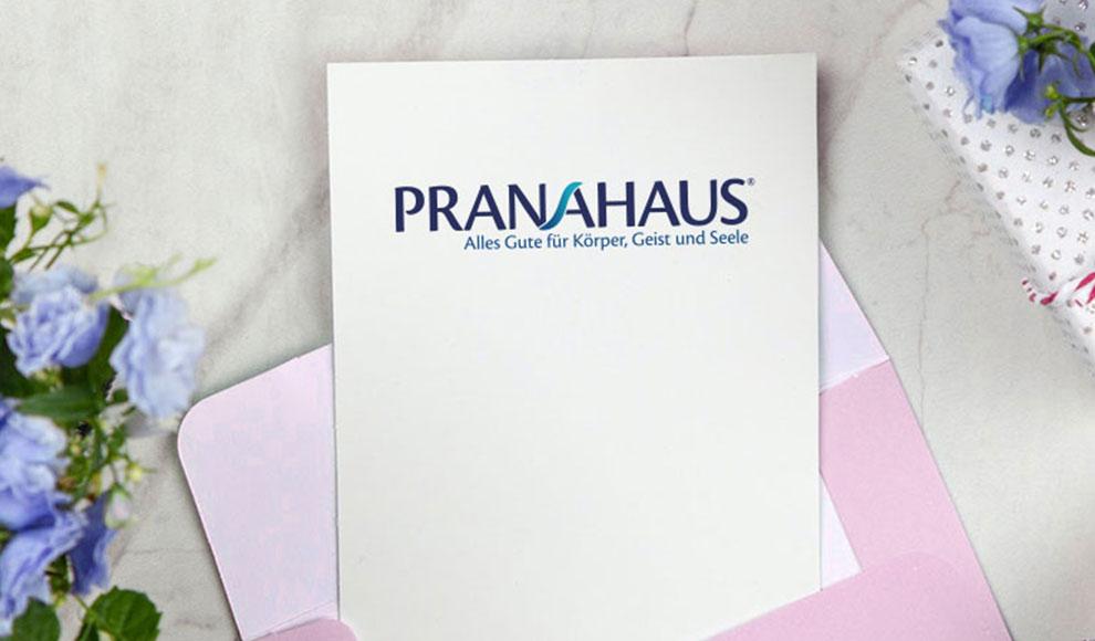 Karte mit PranaHaus-Logo in einem Umschlag, daneben ein Geschenk und ein Blumenstrauß
