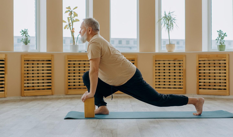 Ein älterer Mann mit Bart übt Yoga in der Wohnung