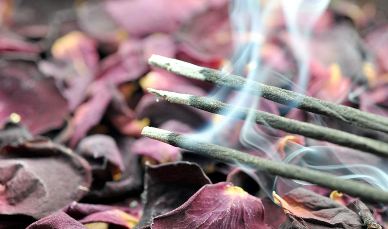 Drei brennende Räucherstäbchen auf getrockneten Rosenblättern