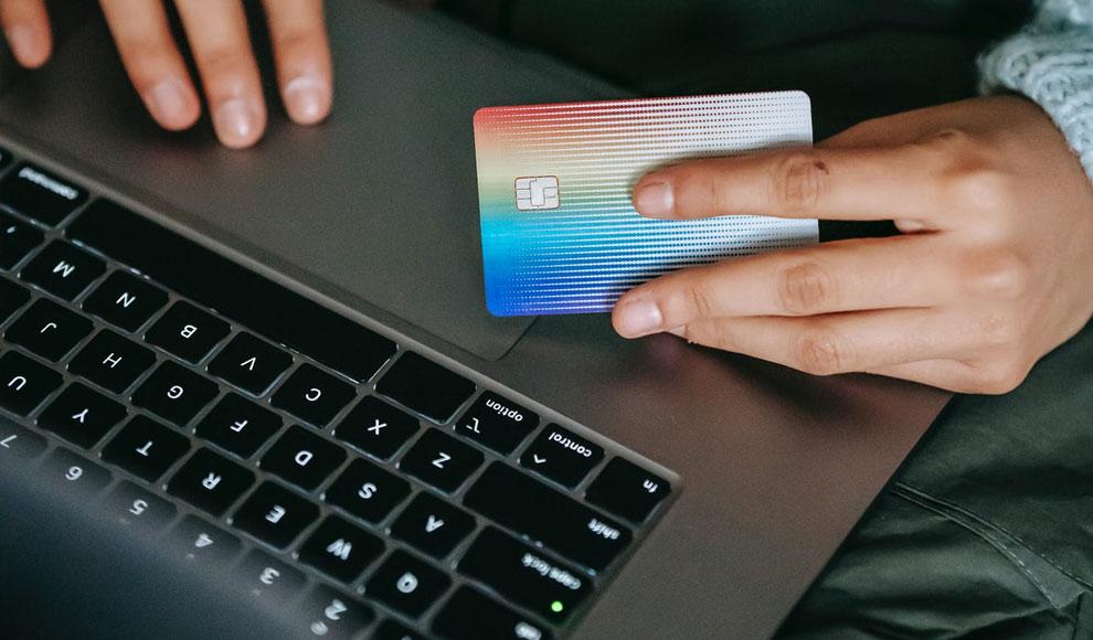 Der Bildausschnitt zeigt ein Notebook und Hände, die eine Kreditkarte halten.