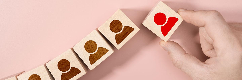 Auf einer beigen Fläche sind mehrere Holzklötzchen angeordnet. Alle zeigen das gleiche Piktogramm einer Person. Eines ist rot eingefärbt. Diese Klötzchen wird von einer Hand aus der Reihe gezogen.