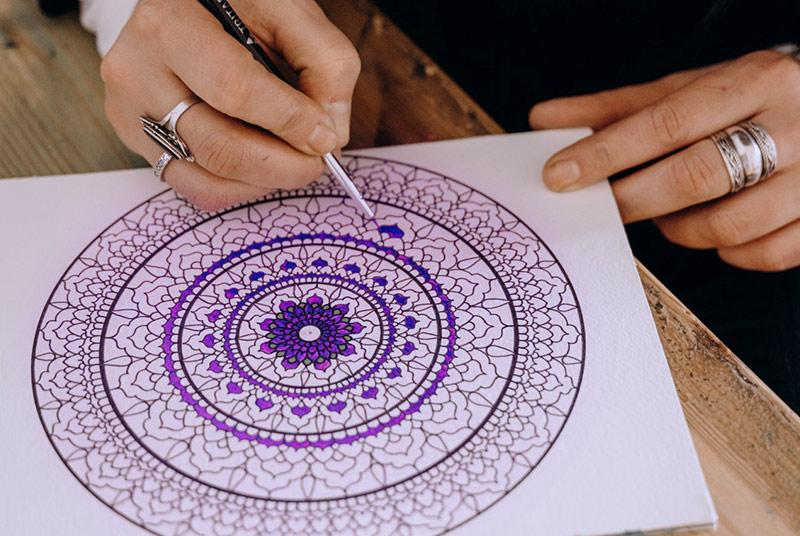 Ein in violetten Tönen gehaltenenes Mandala auf weißem Papier.
